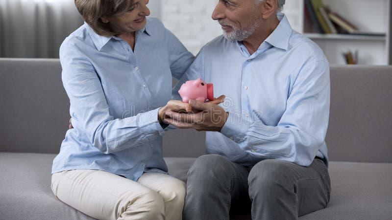 Pares de envelhecimento que sentam-se no sofá com mealheiro, dinheiro de salvamento para o sonho, futuro foto de stock