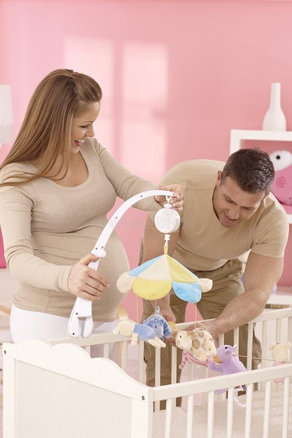 Pares de espera felizes na sala do bebê fotografia de stock