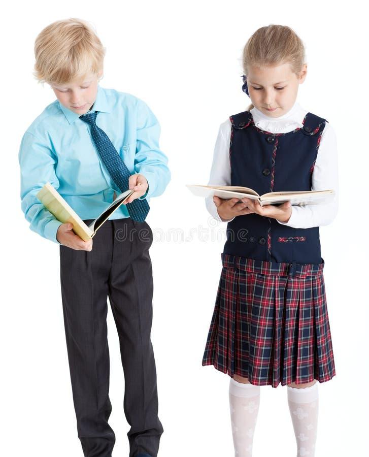 Pares de estudantes novos em livros de leitura da farda da escola junto, fundo branco isolado fotos de stock