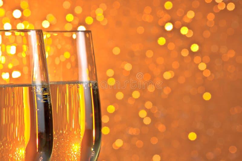 Pares de flautas de un champán en fondo del bokeh de la luz ámbar anaranjada y imagenes de archivo