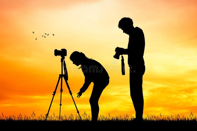 Pares de fotógrafo no por do sol ilustração royalty free
