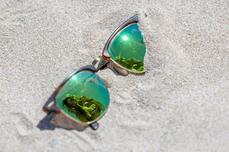 Pares de gafas de sol en la playa con una reflexión de un hermoso foto de archivo