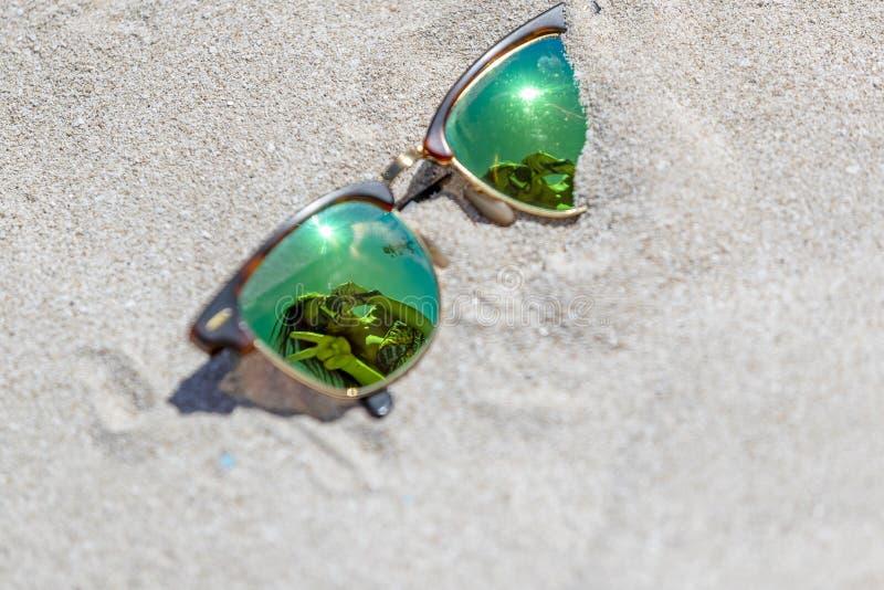 Pares de gafas de sol en la playa con una reflexión de un hermoso foto de archivo libre de regalías
