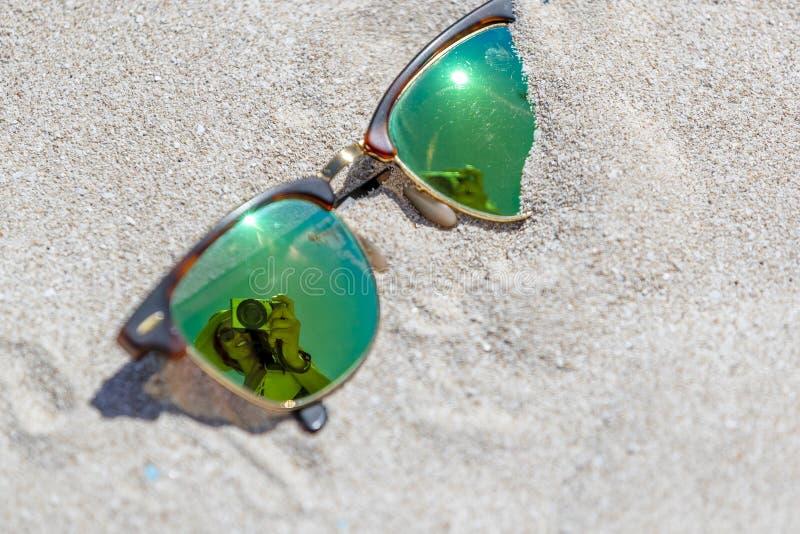 Pares de gafas de sol en la playa con una reflexión de un hermoso fotografía de archivo libre de regalías