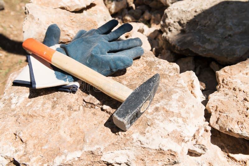 Pares de guantes protectores y de martillo en piedra en emplazamiento de la obra Maruggio, Puglia, Italia imágenes de archivo libres de regalías