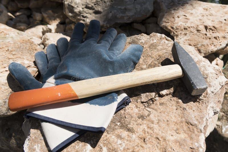 Pares de guantes protectores y de martillo en piedra en emplazamiento de la obra Maruggio, Puglia, Italia imagen de archivo