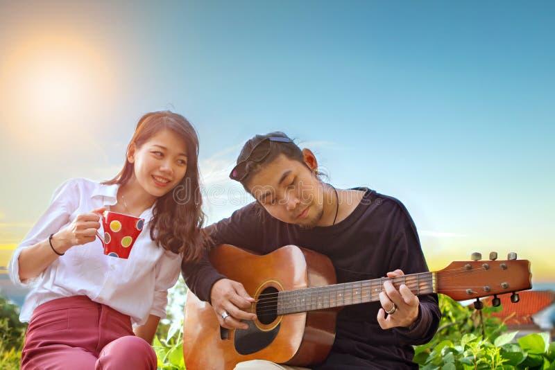 Pares de homem mais novo e de mulher asiáticos que relaxam jogando a guitarra mim fotografia de stock