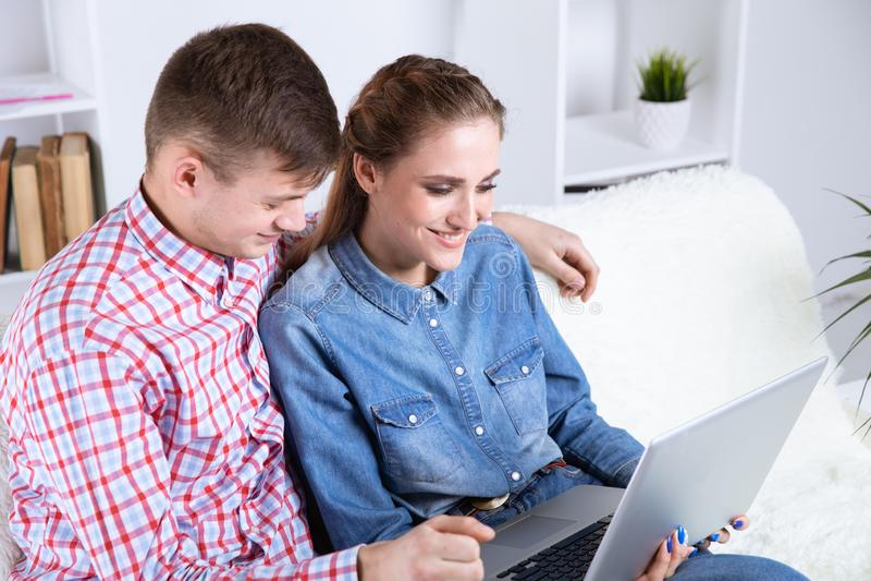 Pares de homem novo e de mulher em linha no Internet que senta-se em um sofá em casa foto de stock