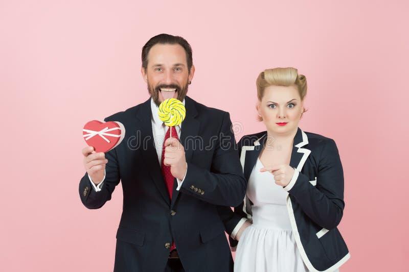 Pares de homens de negócios que amam doces e presentes tiro do conceito do Valentim no estúdio Homem no terno preto com pirulito fotos de stock royalty free