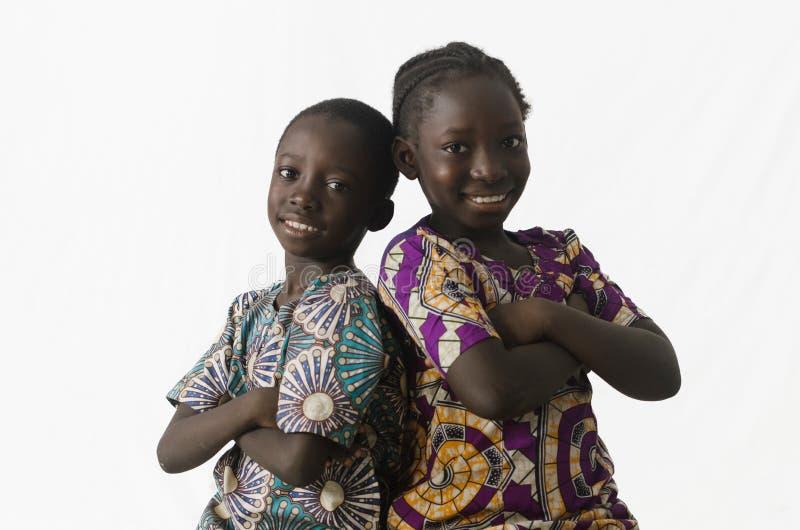 Pares de irmão africano e de irmã que levantam no estúdio, isolados foto de stock royalty free