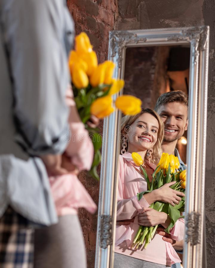 Pares de irradiação alegres que sorriem ao olhar no espelho imagens de stock royalty free