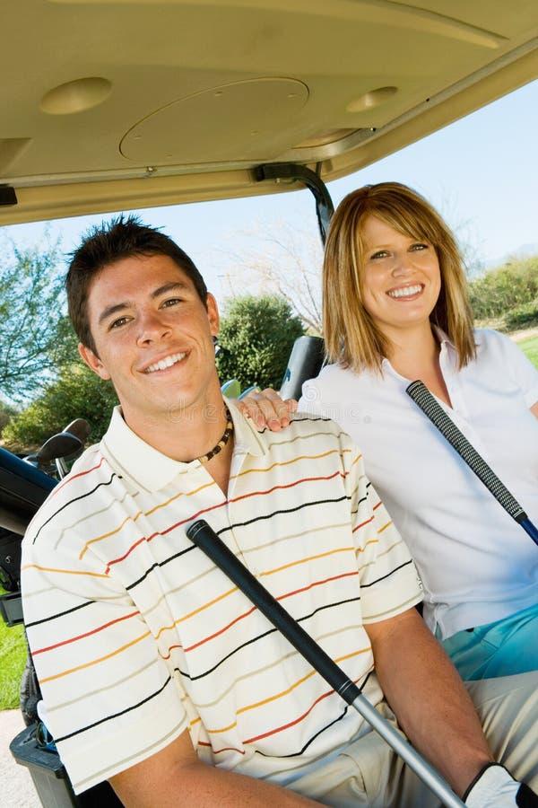 Pares de jogadores de golfe que montam no carro de golfe foto de stock