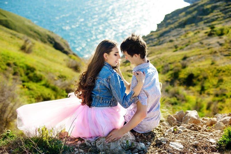 Pares de la belleza que se relajan en campo de trigo junto Novia adolescente y novio que se divierten al aire libre, besándose y imágenes de archivo libres de regalías