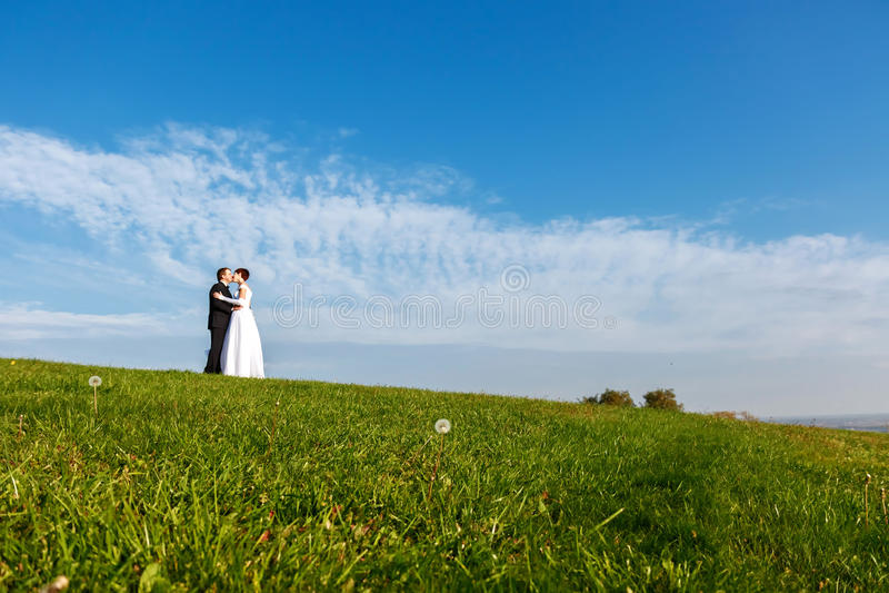 Pares de la boda al aire libre en fondo del cielo azul fotos de archivo libres de regalías