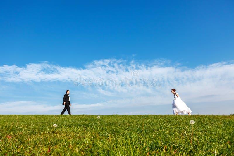 Pares de la boda al aire libre en fondo del cielo azul foto de archivo libre de regalías