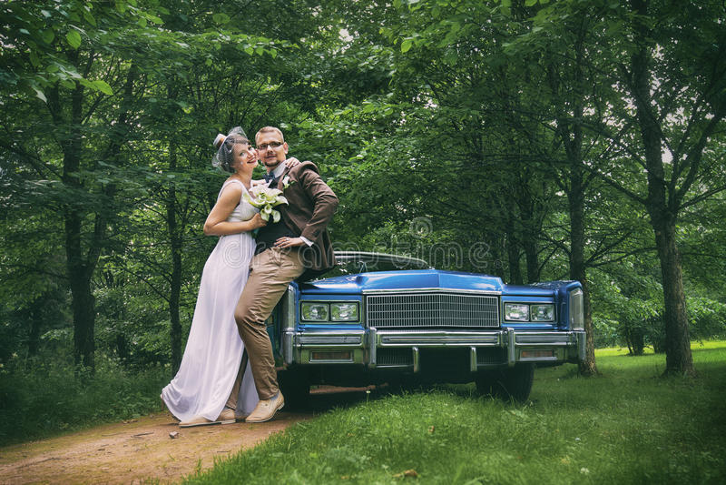 Pares de la boda cerca del coche nupcial fotografía de archivo