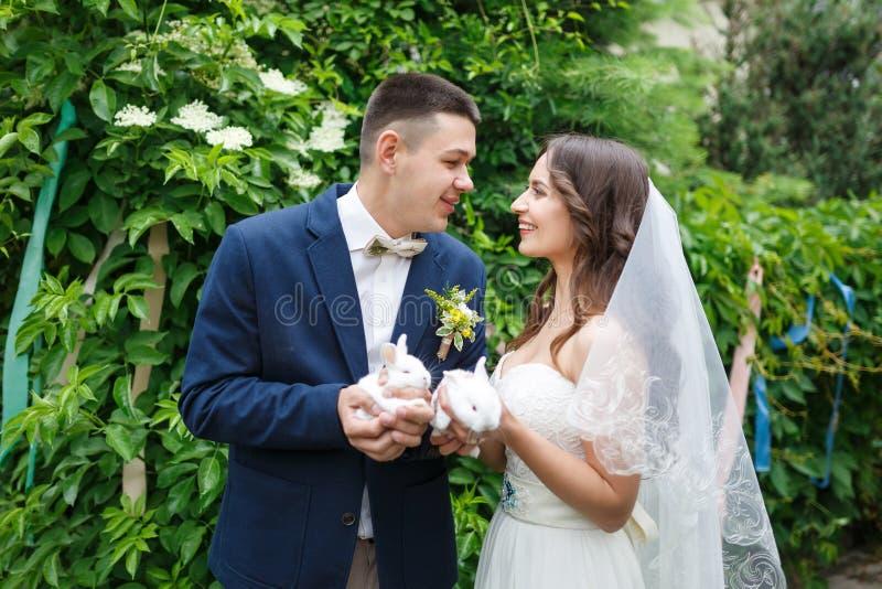 Pares de la boda con dos pequeños conejos imagenes de archivo