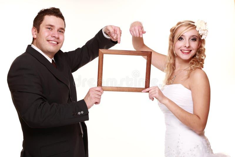 Pares de la boda con el marco vacío para las fotos imagenes de archivo