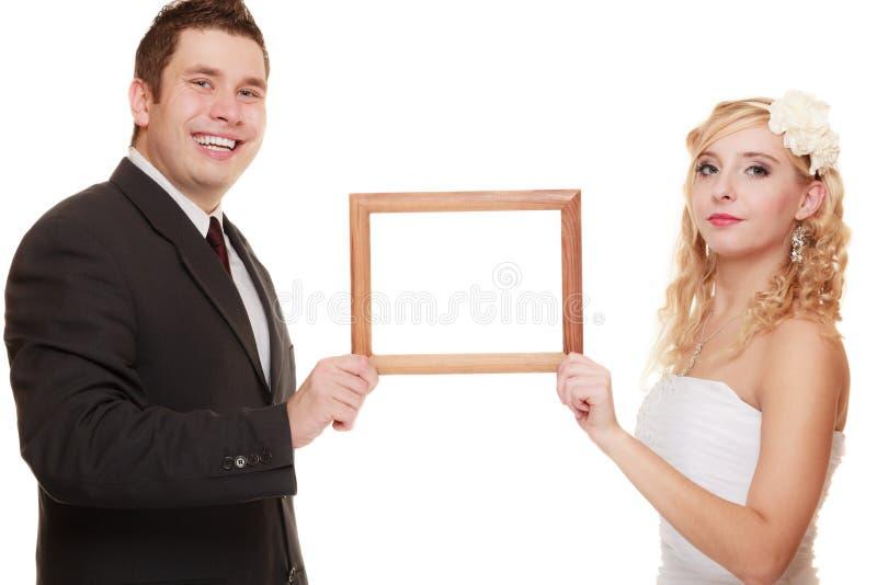 Pares de la boda con el marco vacío para las fotos fotografía de archivo