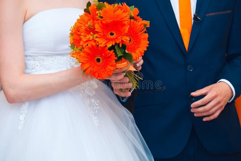 Pares de la boda con el ramo rojo fotografía de archivo libre de regalías