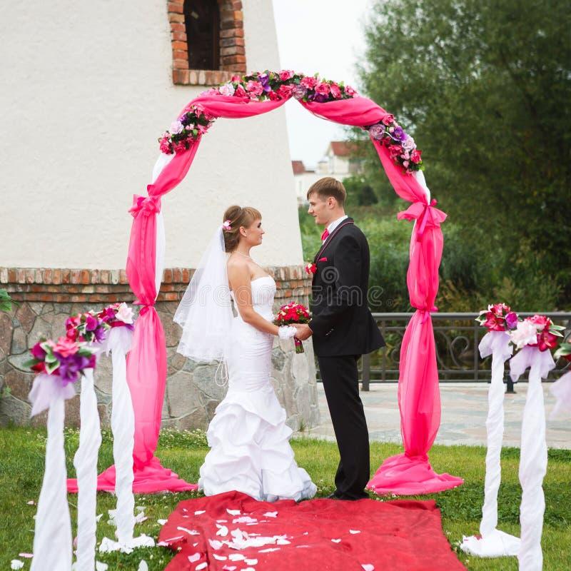 Pares de la boda en el arco imagen de archivo