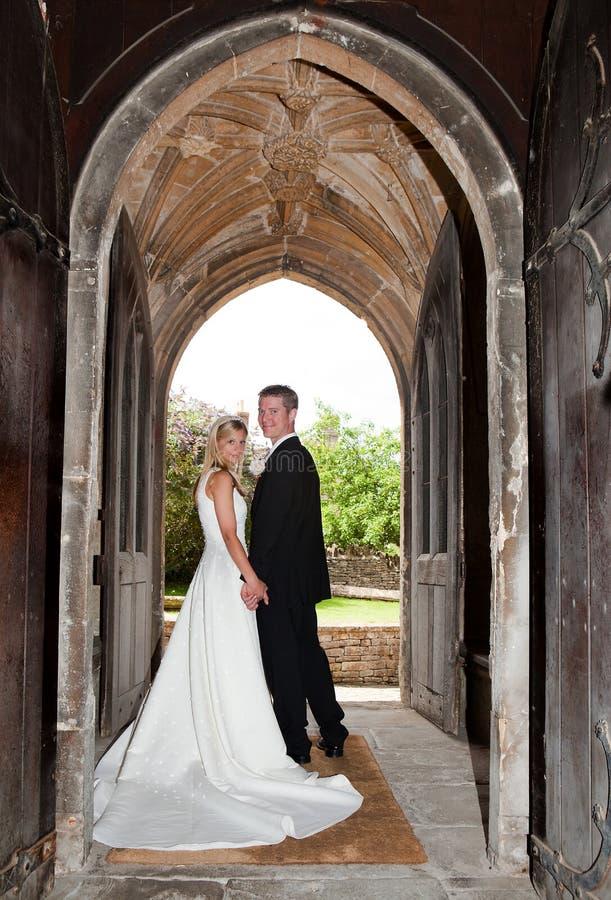 Pares de la boda en entrada de la iglesia fotos de archivo libres de regalías