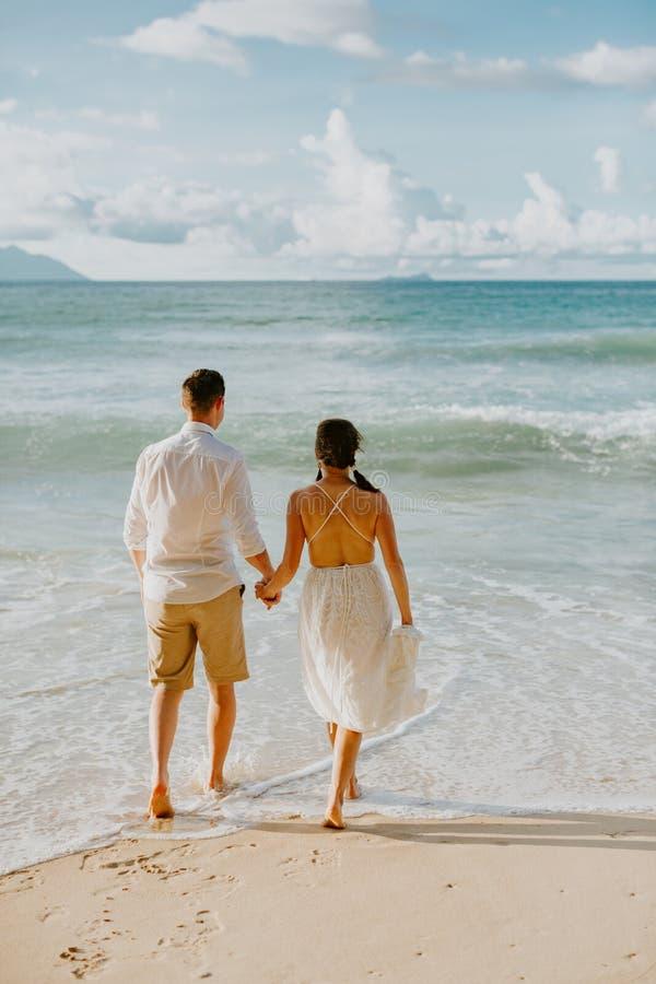 Pares de la boda de la luna de miel en la playa en la puesta del sol foto de archivo libre de regalías