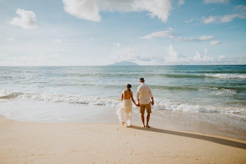 Pares de la boda de la luna de miel en la playa en la puesta del sol imagen de archivo
