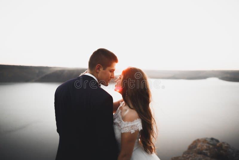 Pares de la boda, novio, novia que presenta cerca del mar en puesta del sol fotos de archivo