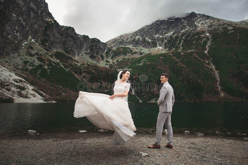 Pares de la boda que caminan cerca del lago en las monta?as de Tatra en Polonia Morskie Oko D?a de verano hermoso fotos de archivo
