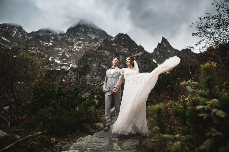 Pares de la boda que caminan cerca del lago en las monta?as de Tatra en Polonia Morskie Oko D?a de verano hermoso foto de archivo