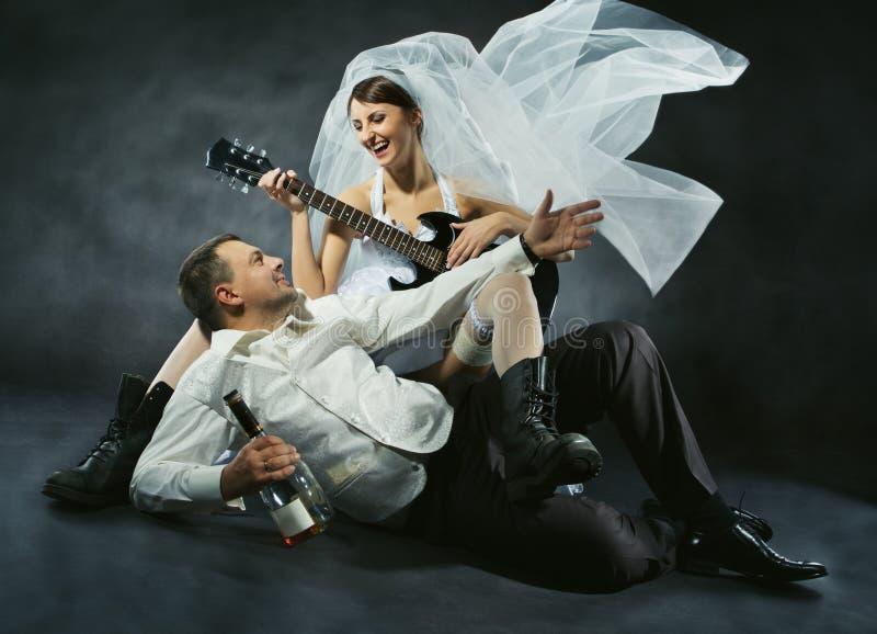Pares de la boda que celebran, cantando, bebiendo y tocando la guitarra imagenes de archivo
