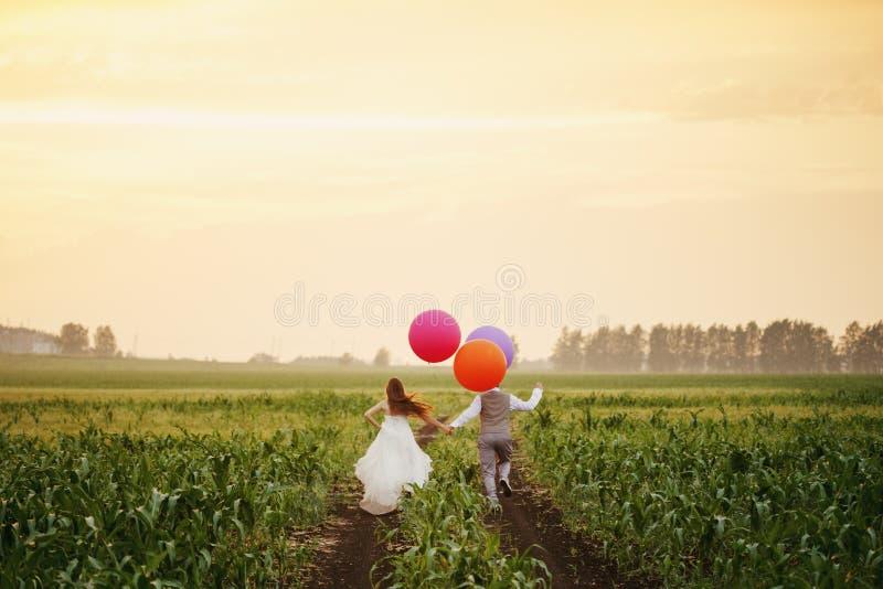 Pares de la boda que corren lejos en el campo foto de archivo