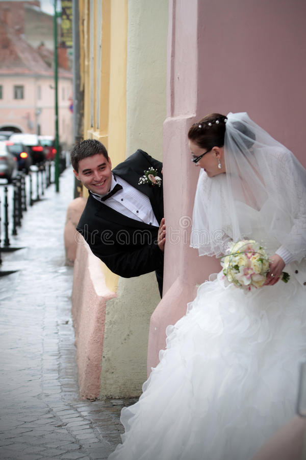 Pares de la boda que juegan escondite imagen de archivo