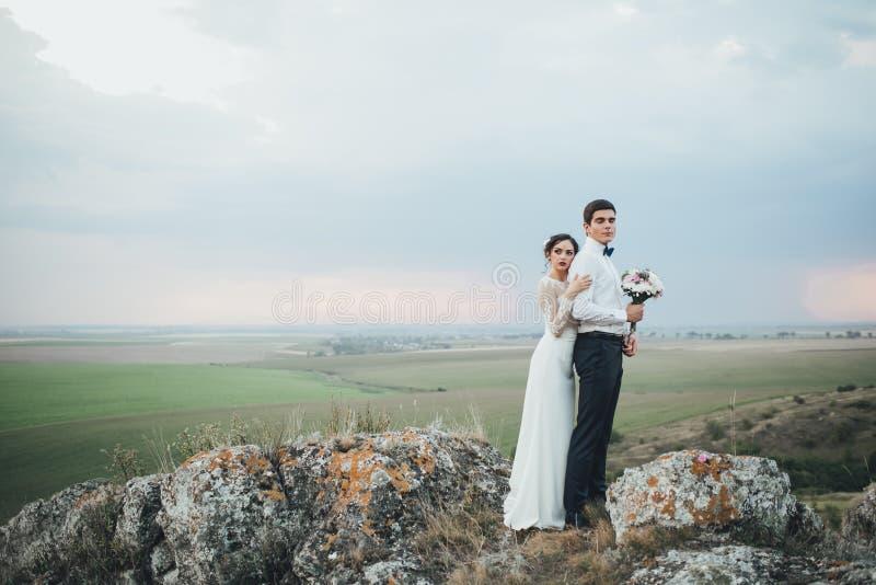Pares de la boda que miran en colina de la montaña en puesta del sol imagenes de archivo