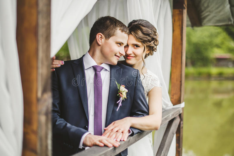 Pares de la boda que presentan en el embarcadero imagenes de archivo