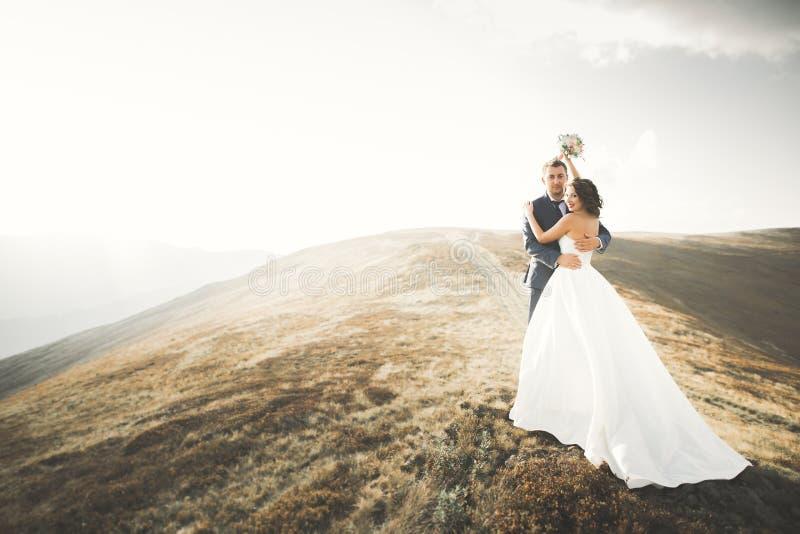 Pares de la boda que presentan en puesta del sol en el día de boda Novia y novio en amor fotografía de archivo