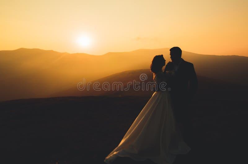 Pares de la boda que presentan en puesta del sol en el día de boda Novia y novio en amor imagenes de archivo