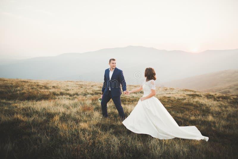 Pares de la boda que presentan en puesta del sol en el día de boda Novia y novio en amor foto de archivo libre de regalías
