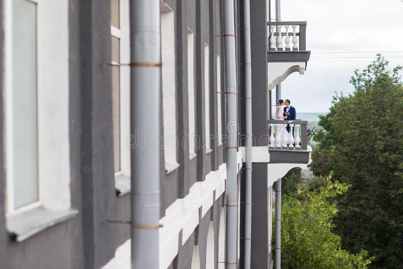 Pares de la boda que se colocan en el balcón foto de archivo libre de regalías
