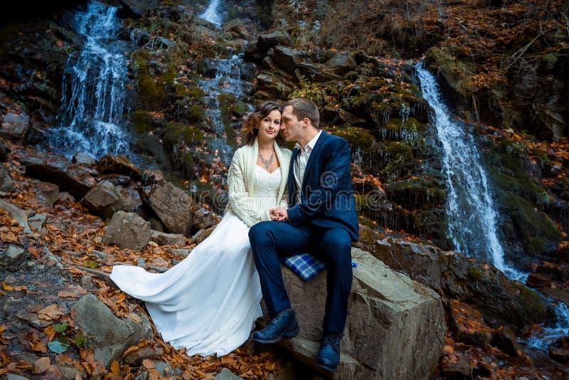 Pares de la boda que se sientan en la piedra y la presentación Cascada en fondo de las montañas Caída foto de archivo libre de regalías