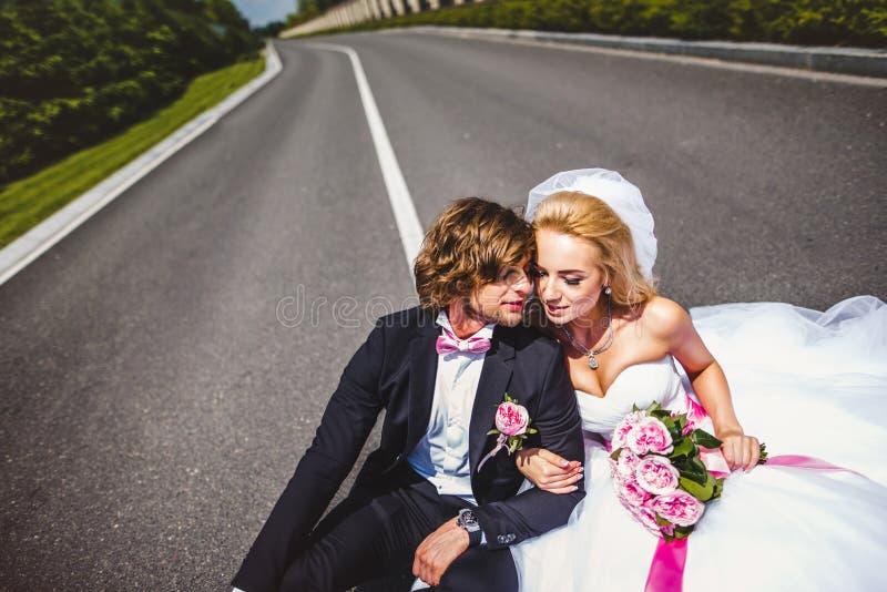 Pares de la boda que se sientan en la tierra fotografía de archivo libre de regalías