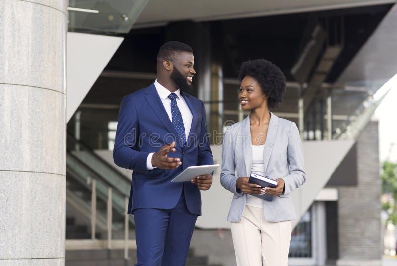 Pares de la charla amistosa de los empleados africanos al aire libre fotos de archivo
