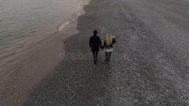 Pares de la datación que caminan en la costa que lleva a cabo las manos, flores que llevan de la muchacha, romance fotos de archivo