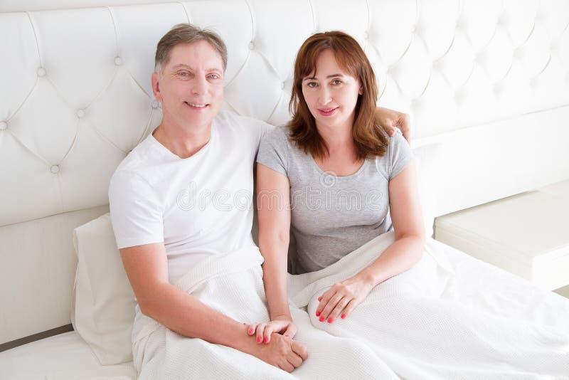 Pares de la Edad Media con las arrugas que se sientan en cama Camiseta en blanco de la plantilla Mujer y hombre en dormitorio For fotos de archivo