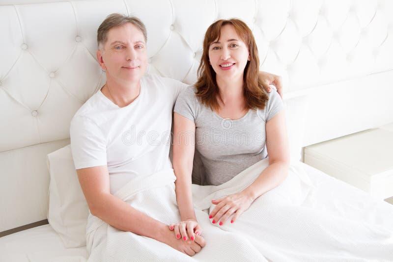 Pares de la Edad Media con las arrugas que se sientan en cama Camiseta en blanco de la plantilla Mujer y hombre en dormitorio For imagen de archivo