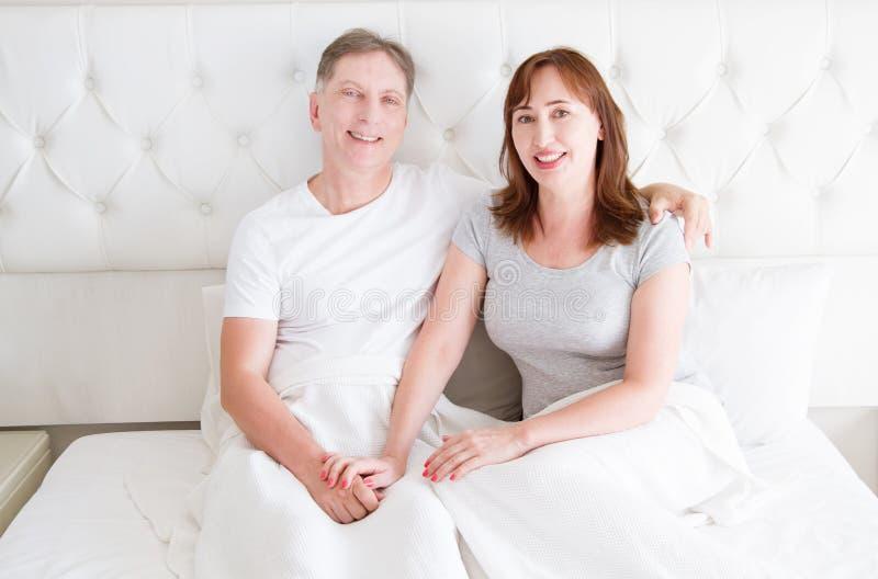 Pares de la Edad Media con las arrugas que se sientan en cama Camiseta en blanco de la plantilla Mujer y hombre en dormitorio For foto de archivo