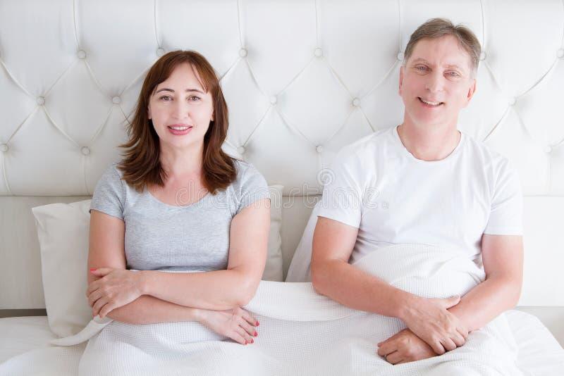 Pares de la Edad Media con las arrugas que se sientan en cama Camiseta en blanco de la plantilla Mujer y hombre en dormitorio For fotografía de archivo libre de regalías