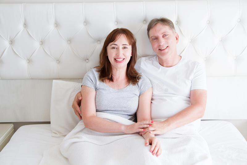 Pares de la Edad Media con las arrugas que se sientan en cama Camiseta en blanco de la plantilla Mujer y hombre en dormitorio For imagen de archivo libre de regalías