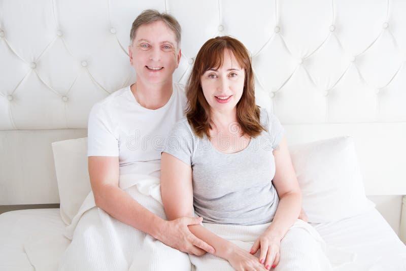 Pares de la Edad Media con las arrugas que se sientan en cama Camiseta en blanco de la plantilla Mujer y hombre en dormitorio con imagen de archivo libre de regalías